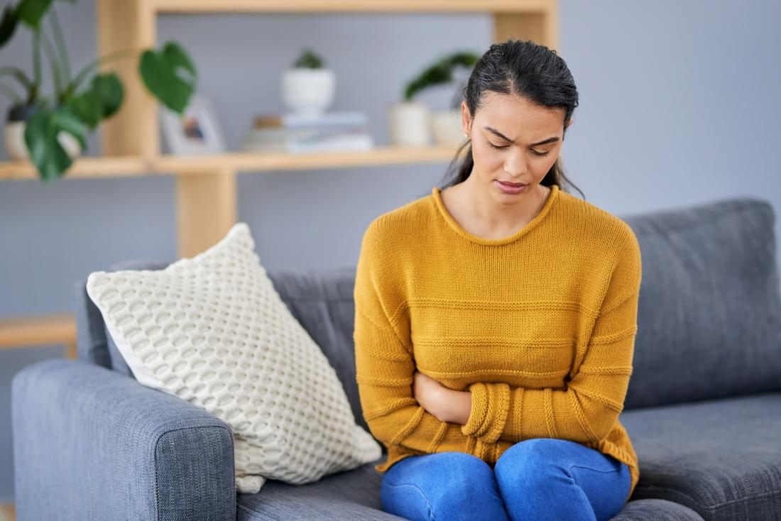 a woman holding her stomach because she suffers from Bowel disorders