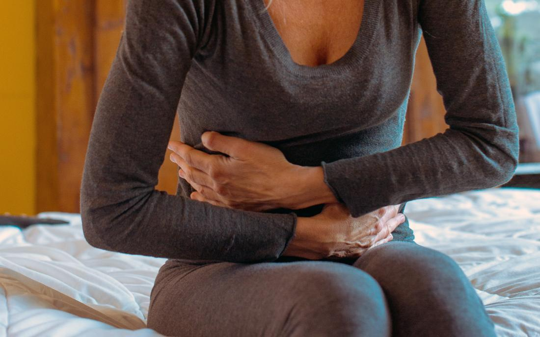 a woman holding her stomach and wondering Can nausea cause constipation