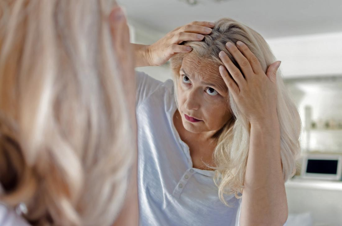 a woman inspecting her hair and wondering if a lack of ferritin is causing hair loss.