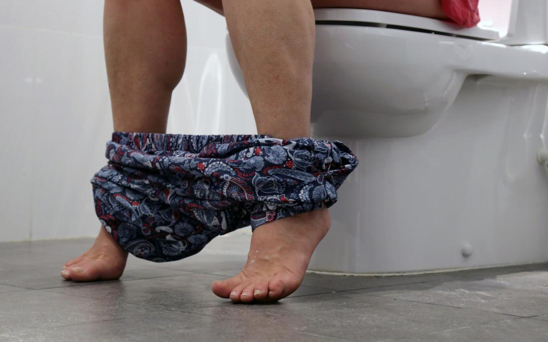 a woman sat on the toilet because she has proctitis