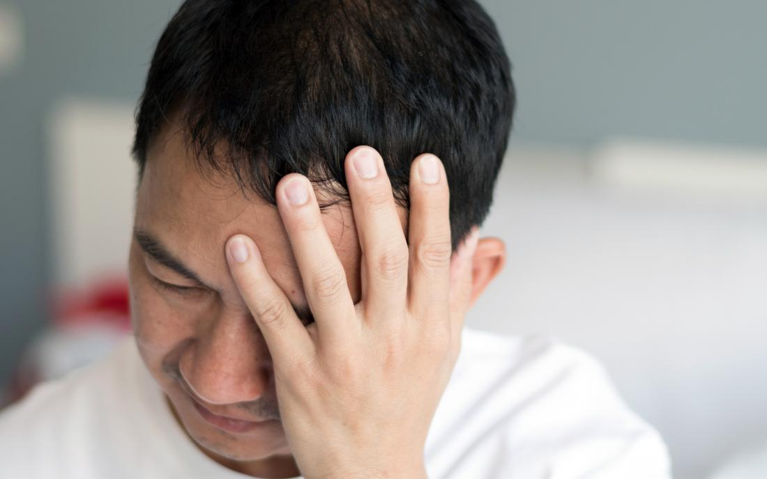 a man experiencing a headache because he is in Concussion recovery