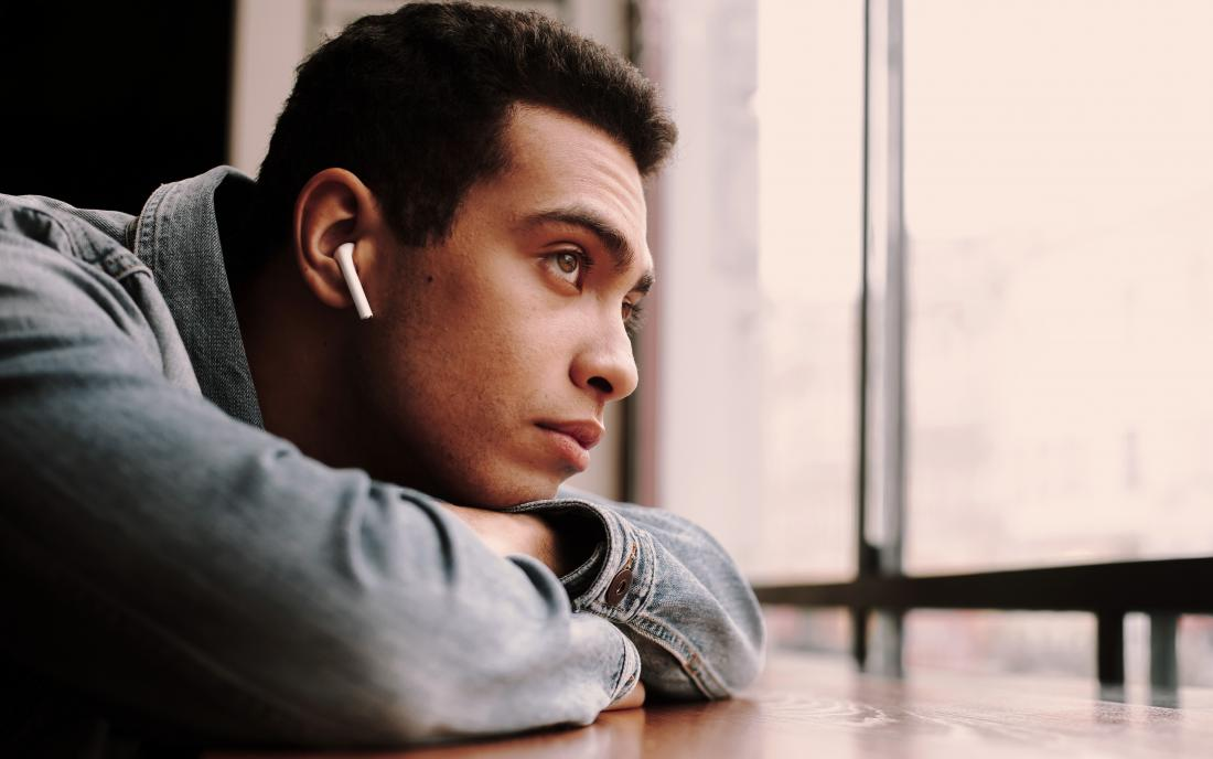 a man with arfid looking pensive as he sits at table and looks out a window.