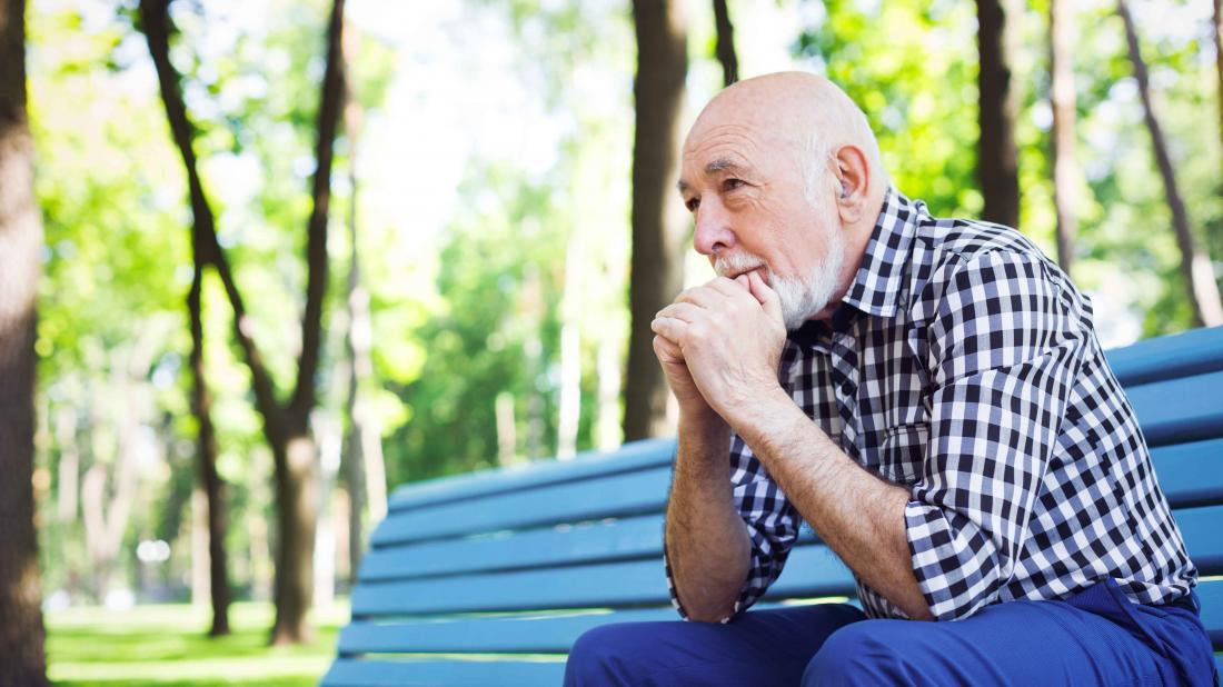 a man with Diabetes and anxiety sat looking pensive on a park bench