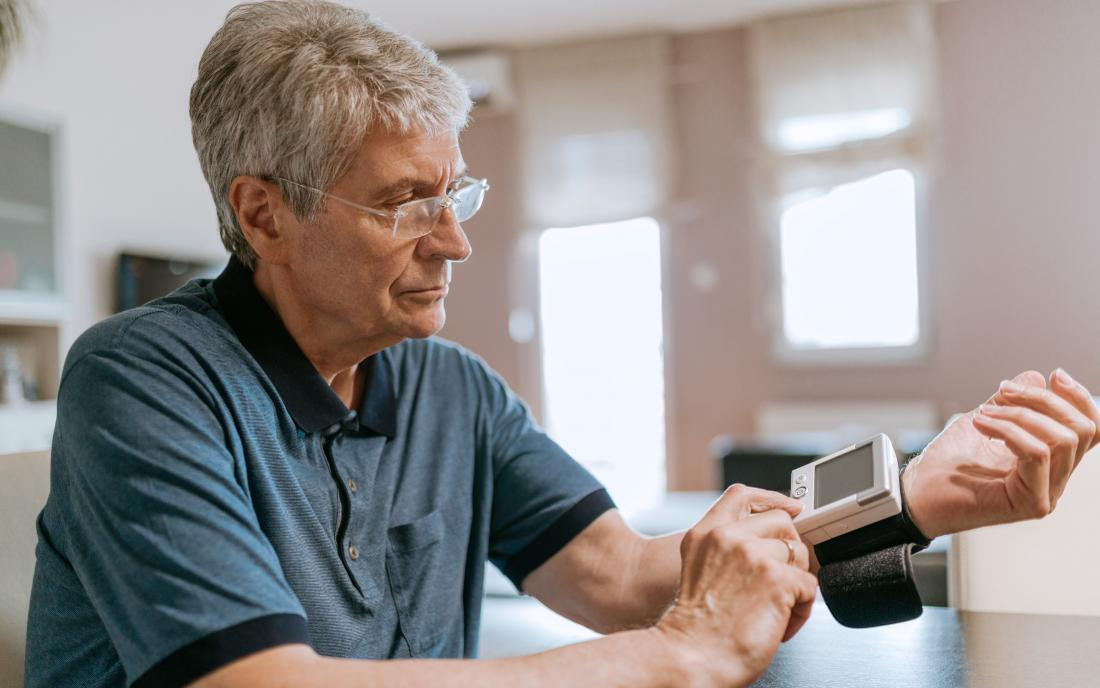 a man using a blood pressure device at home that has a screen attached to explain the readings.