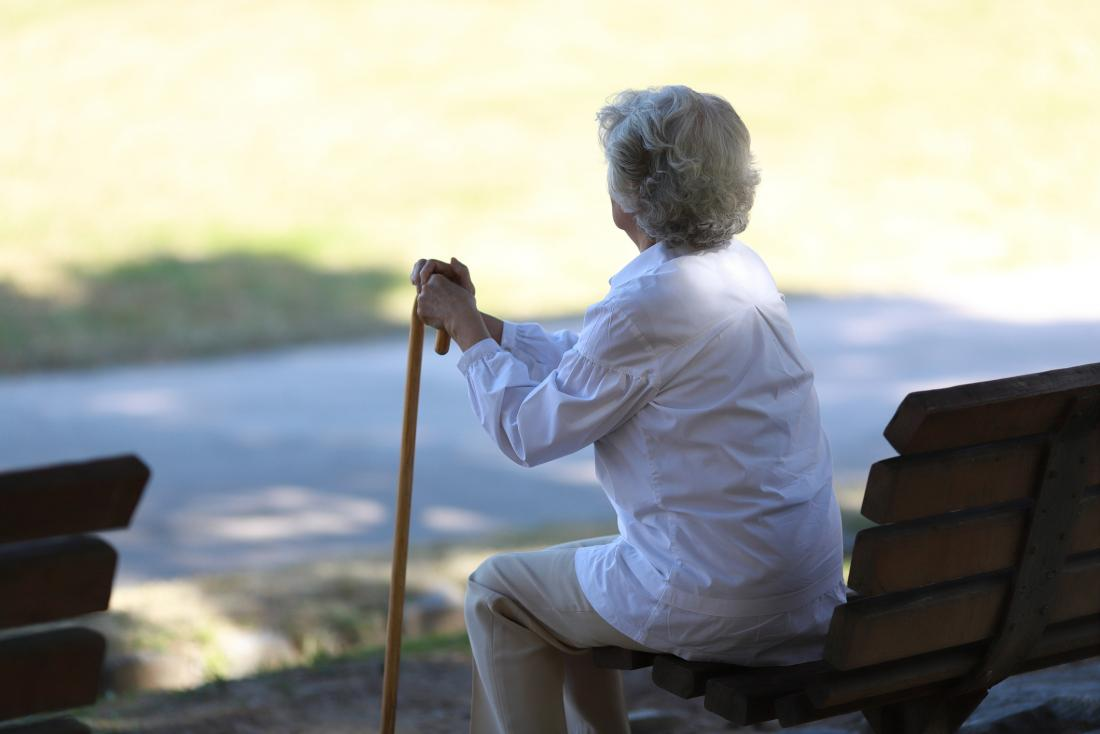 older woman with her back turned to the camera leaning on a cane