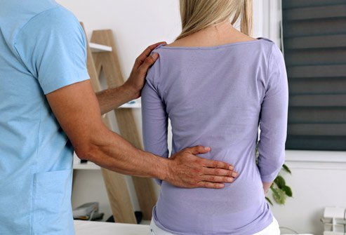 Picture of a healthprofessional with his hand on a patien'ts lower back.