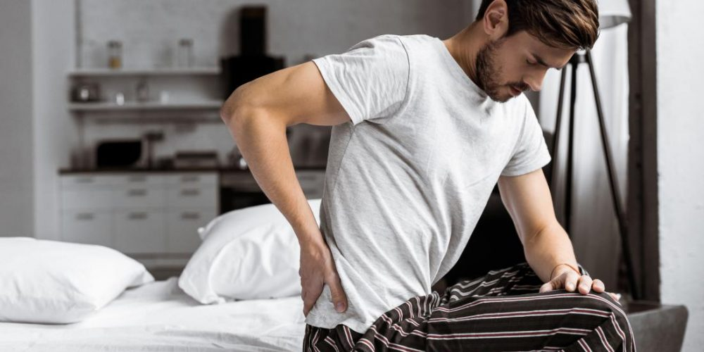 What can cause lower back and testicle pain?